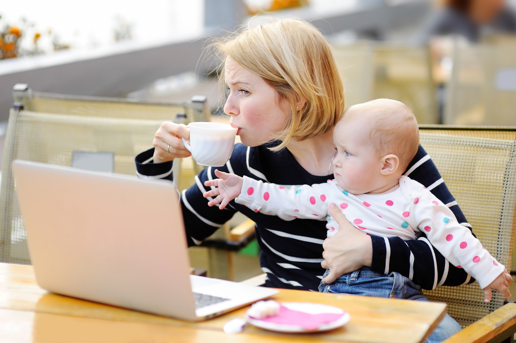 Busy young mother holding baby and trying to make money blogging from home.